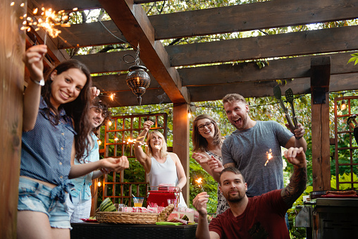 Summer barbecue with girls and boys friends in Quebec Canada. They are around the table and have fun with fireworks. They have around thirty years old, either the Y or millennial generation.
