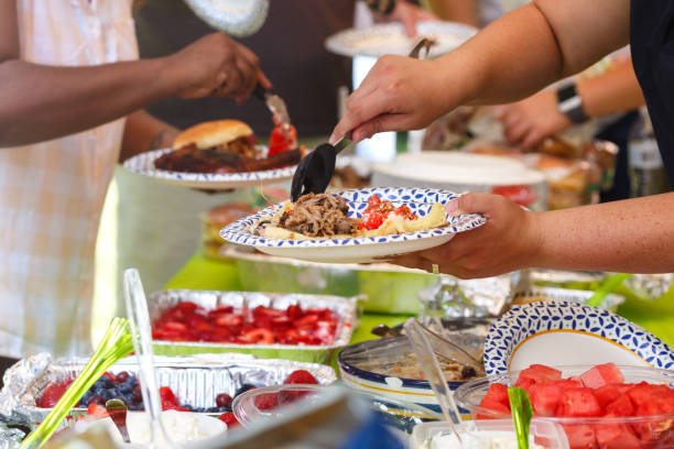 Summer Barbeque Potluck Guests filling plates at a summer cookout picnic stock pictures, royalty-free photos & images