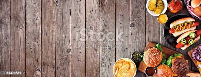 657146780 istock photo Summer BBQ corner border with hot dogs and hamburgers, top view over a dark wood banner background 1254094834