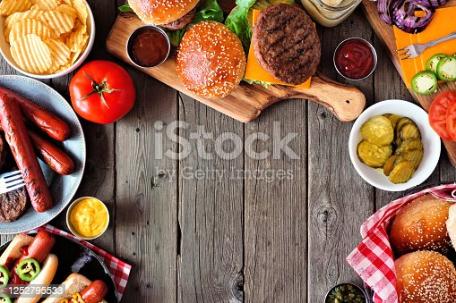 657146780 istock photo Summer BBQ food frame with hot dog and hamburger buffet, above view over a dark wood background 1252795533