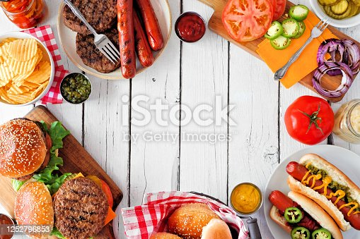 657146780 istock photo Summer BBQ food frame with hot dog and hamburger buffet, overhead against a white wood background 1252796853