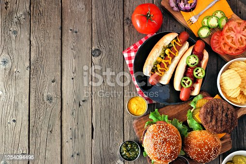 657146780 istock photo Summer BBQ food side border with hot dog and hamburger buffet, overhead on a dark wood background 1254094495