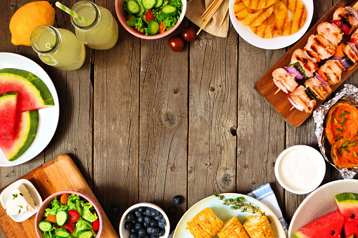 istock Summer BBQ or picnic food frame, top view over a wood background 1152924903
