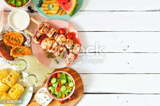 Summer BBQ or picnic food side border. Selection of grilled meat, fruits, salad and potatoes. Above view over a white wood background. Copy space.