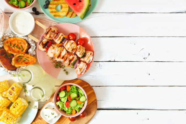 Summer BBQ or picnic food side border, above view over a white wood background Summer BBQ or picnic food side border. Selection of grilled meat, fruits, salad and potatoes. Above view over a white wood background. Copy space. picnic stock pictures, royalty-free photos & images