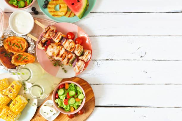 summer bbq or picnic food side border, above view over a white wood background - pasto al sacco foto e immagini stock