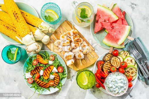 646207652 istock photo Summer bbq party concept - grilled chicken, vegetables, corn, salad, top view 1034954650