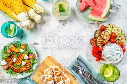 646207652 istock photo Summer bbq party concept - grilled chicken, vegetables, corn, salad, top view 1034954774