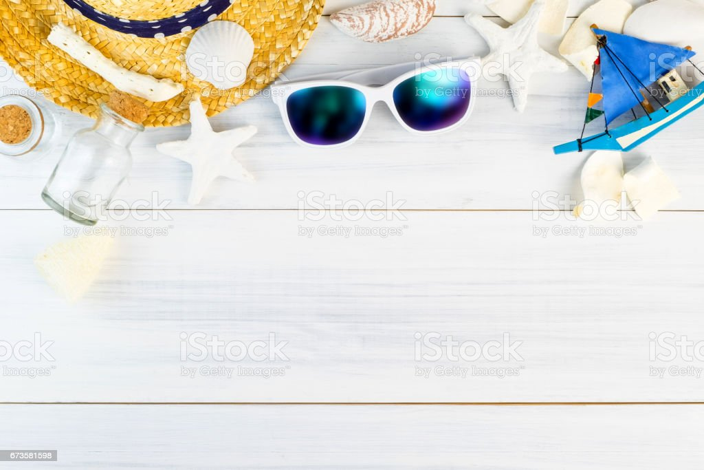 Summer Beach accessories (White sunglasses,starfish,straw hat,glass bottle,shell) on white plaster wood table top view,Summer vacation concept,Leave space for adding text. stock photo