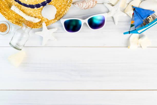 Acessórios de praia verão (óculos de sol brancos, estrela do mar, chapéu de palha, frasco de vidro, casca) em branco gesso vista madeira parte superior de tabela, conceito de férias de verão, deixar espaço para adicionar texto. - foto de acervo