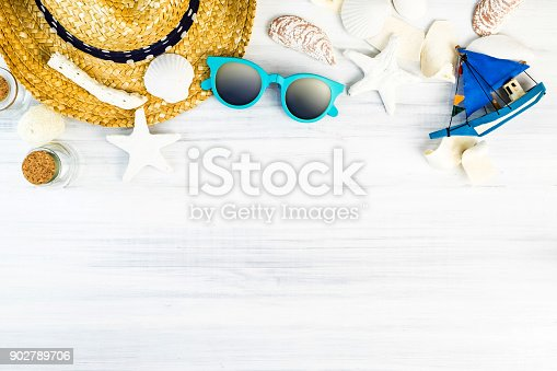 istock Summer Beach accessories (White sunglasses,starfish,straw hat,glass bottle,shell) on white plaster wood table top view,Summer vacation concept,Leave space for adding text 902789706