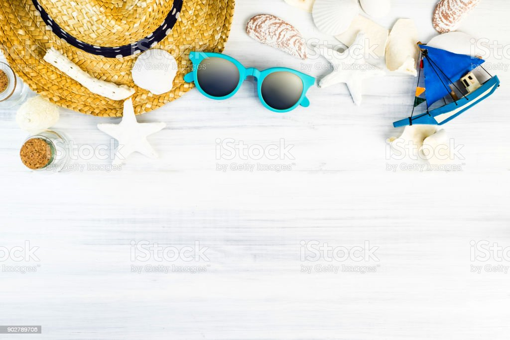 Summer Beach accessories (White sunglasses,starfish,straw hat,glass bottle,shell) on white plaster wood table top view,Summer vacation concept,Leave space for adding text stock photo