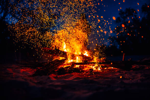 summer beach bonfire with sparks flying around - falò foto e immagini stock