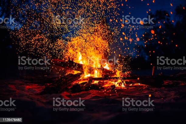 Photo of Summer beach bonfire with sparks flying around