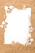 Piece of paper and seashells on the sand