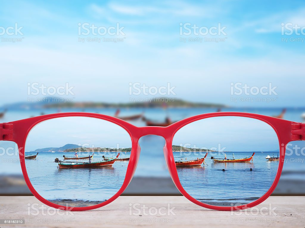 Summer beach focused in red glasses lenses stock photo