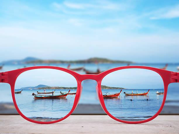 Summer beach focused in red glasses lenses - foto de stock