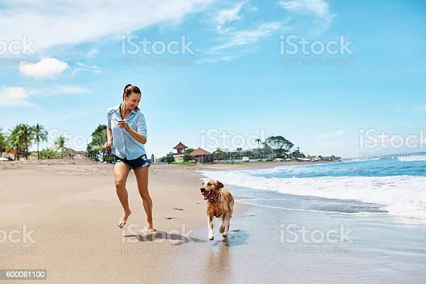 Summer beach fun woman running with dog holidays vacations summer picture id600061100?b=1&k=6&m=600061100&s=612x612&h=ypmb3pu08kur51lsm2ajya cvbxn auidmymazydn0o=