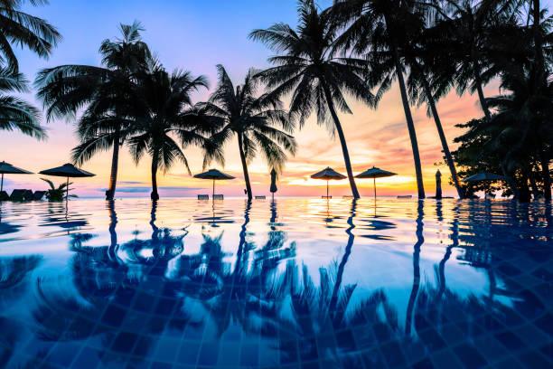 letnia plaża wakacje miejsce wypoczynku, luksusowy basen ośrodek przy plaży z tropikalnym krajobrazem, cichy ciepły zachód słońca, sylwetka i odbicie w wodzie - kurort turystyczny zdjęcia i obrazy z banku zdjęć