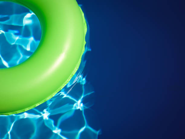 Summer beach pool in turquoise color water with floating bright green donut ring for vacation time stock photo