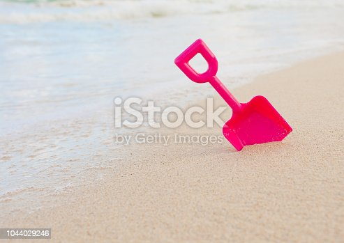 605742160 istock photo Summer beach toy in the sand by the water. 1044029246