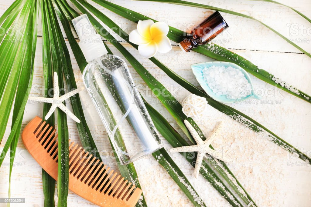 Summer beauty care kit. Bottle of mineral sea salt hair and body spray viewed from above on green palm leaf stock photo