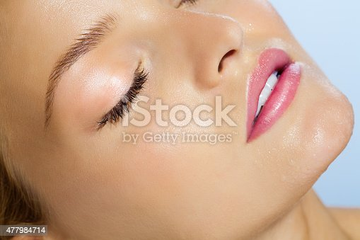 Closeup of beautiful smooth young dewy skin with water drops over sky blue background. Serene woman with eyes closed in summer sun.