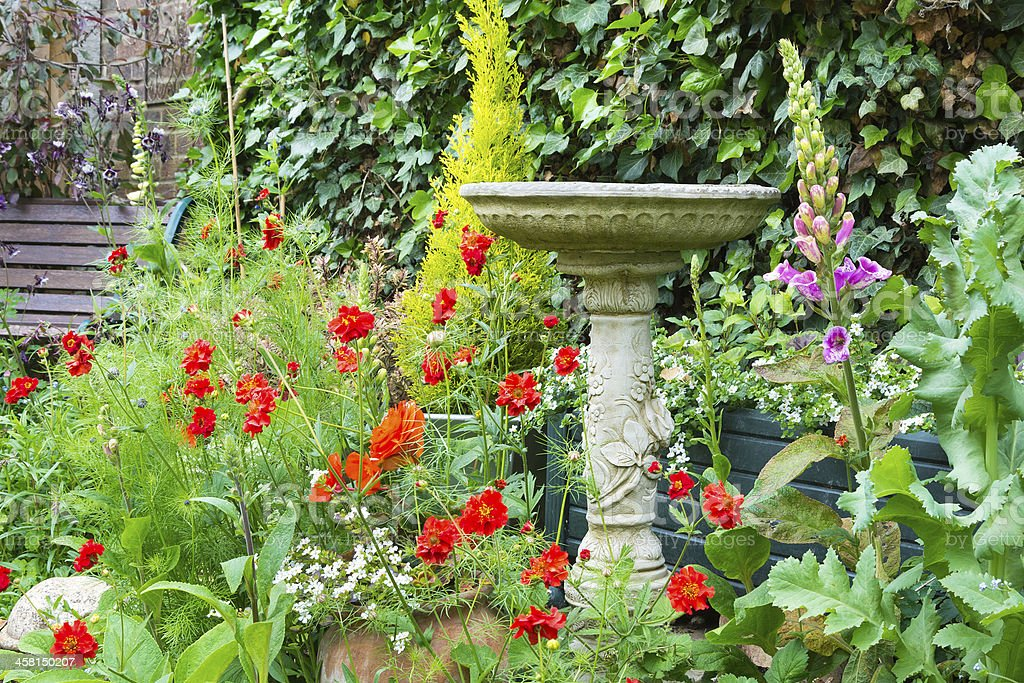 Summer bedding flowers with decorative stone bird bath stock photo
