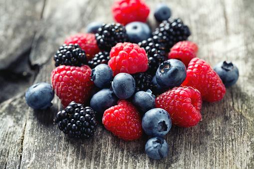 istock summer berries on wooden surface 489662264