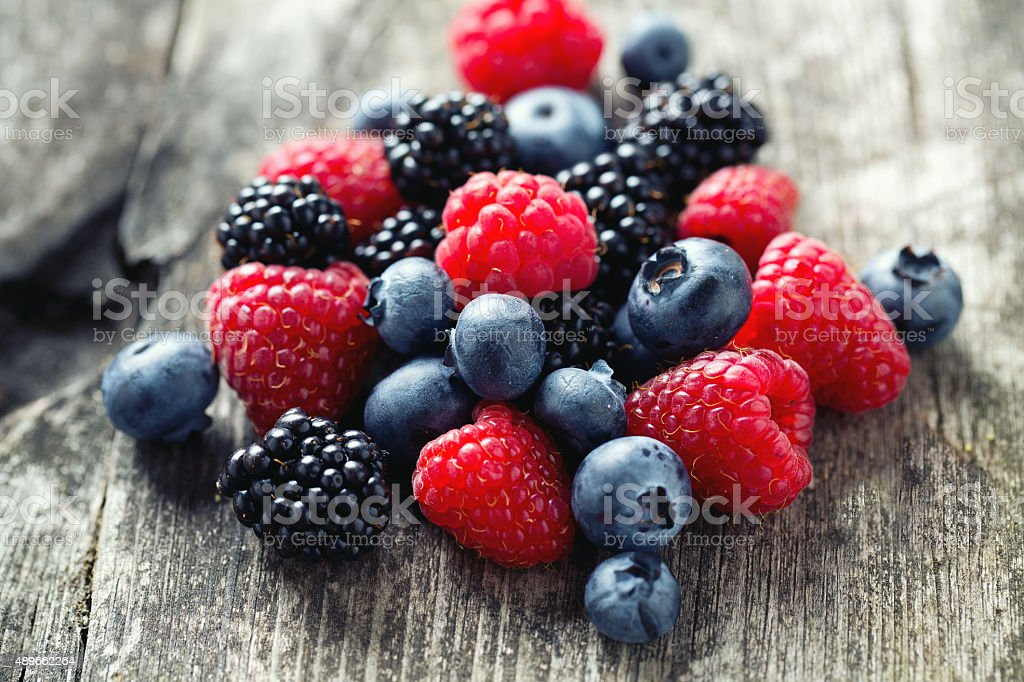 summer berries on wooden surface stock photo