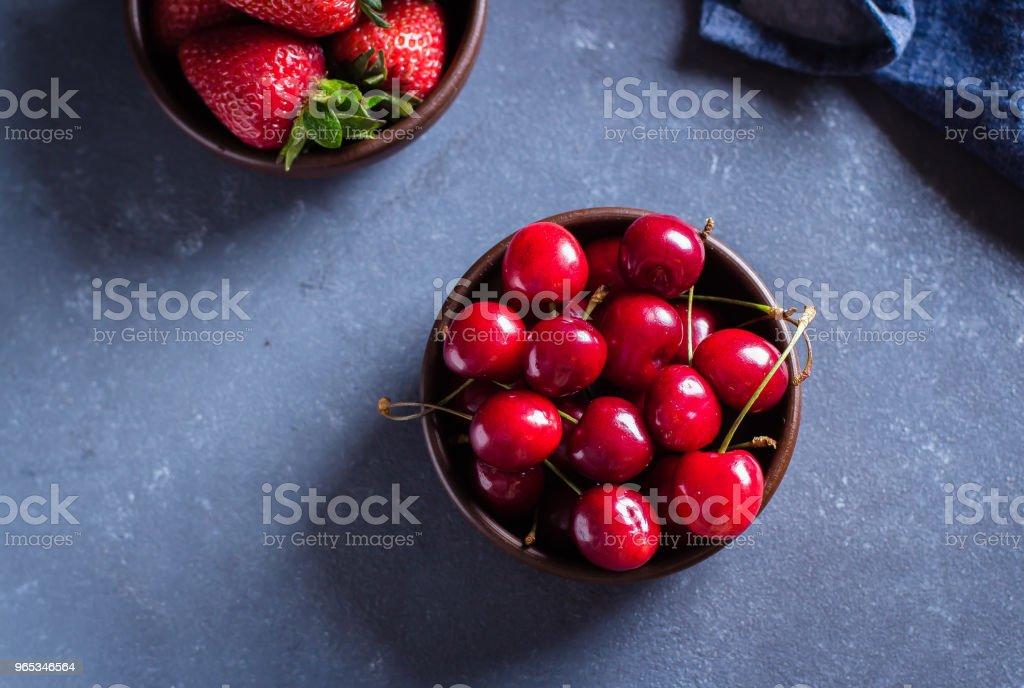 Summer fruits fraise et cerise à la plaque de bois sur fond bleu table en béton. Concept d'une alimentation saine. Vue de dessus. espace copie - Photo de Aliment libre de droits