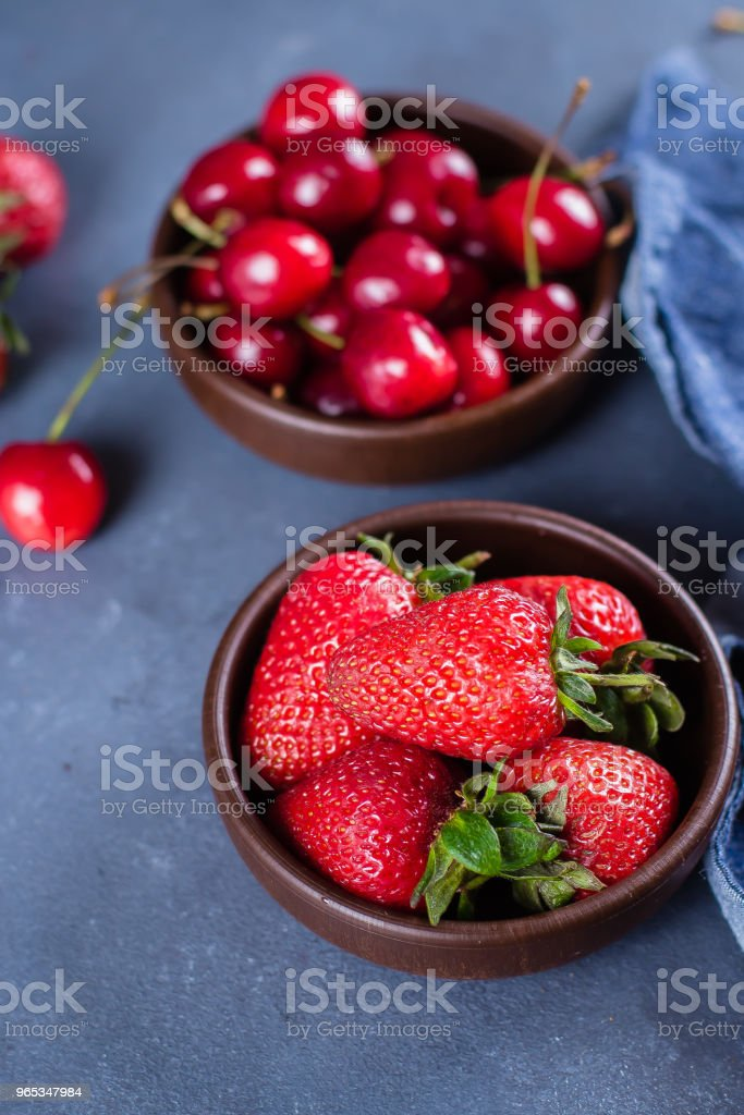 Summer Berries Strawberry and Cherry in wooden plate on blue concrete table background. Healthy Food Concept. zbiór zdjęć royalty-free