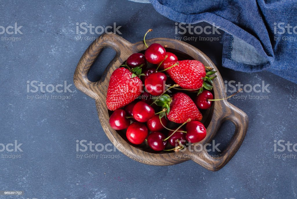 Summer Berries Strawberry and Cherry in wooden plate on blue concrete table background. Healthy Food Concept. Top view, copy space royalty-free stock photo