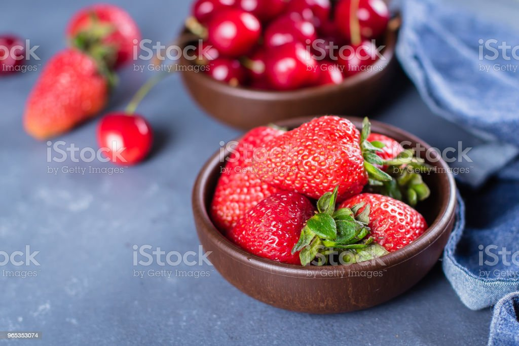 Summer Berries Strawberry and Cherry in wooden plate on blue concrete table background. Healthy Food Concept. royalty-free stock photo