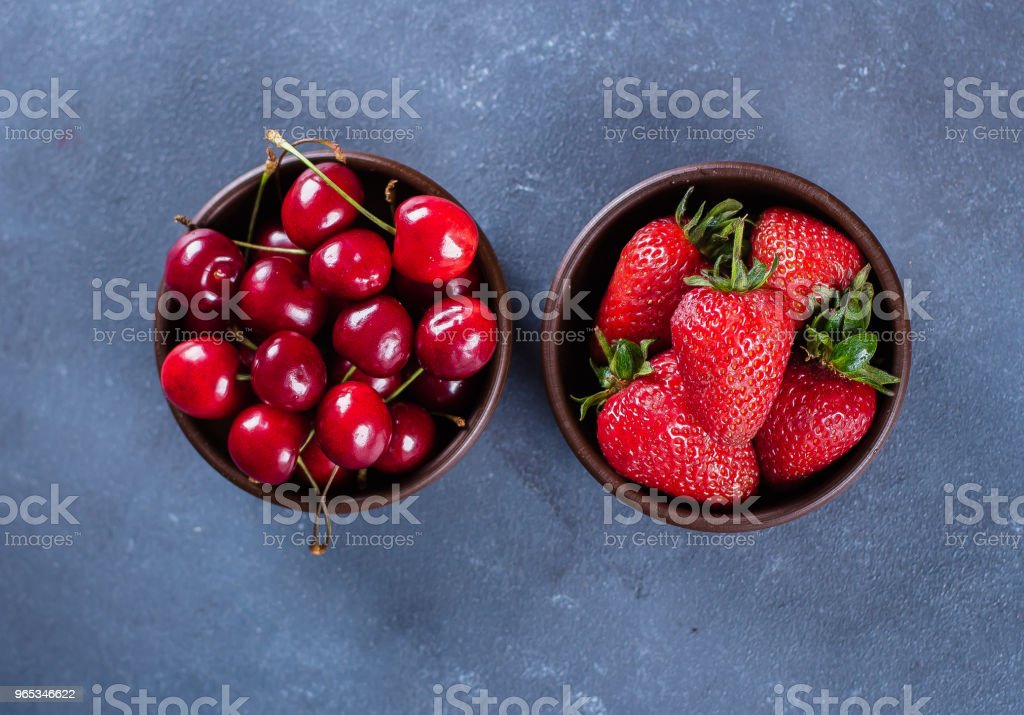 Summer Berries. Two bowl with strawberry and cherryon blue concrete table background. Healthy Food Concept. Top view, copy space royalty-free stock photo