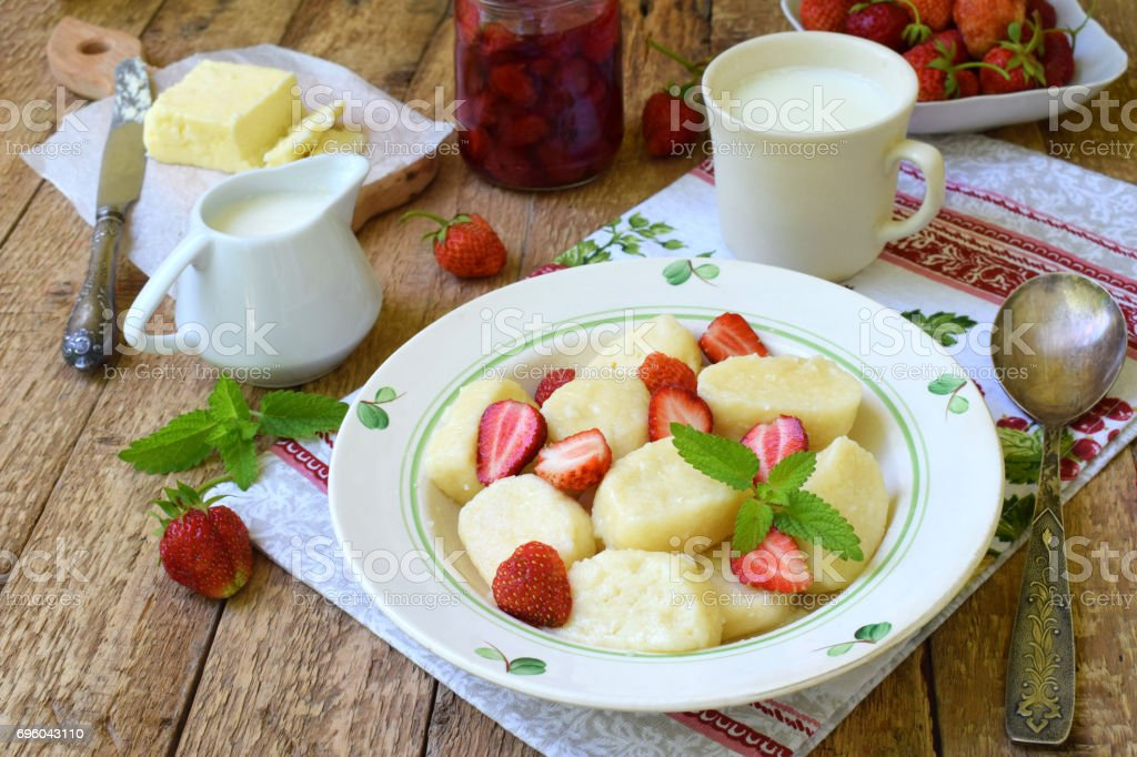 Summer berry breakfast. Sweet lazy pierogi, dumplings with sour cream, butter and strawberry on wooden background. Italian gnocchi. Copy space for your text. stock photo
