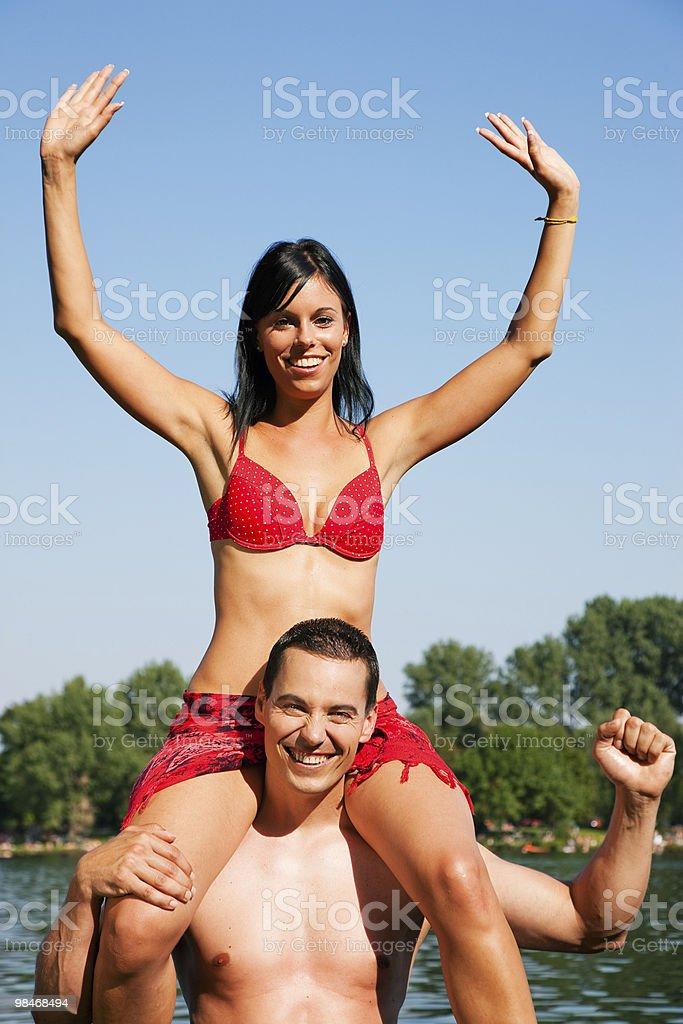 Summer bikini girl sitting on shoulders of man royalty-free stock photo