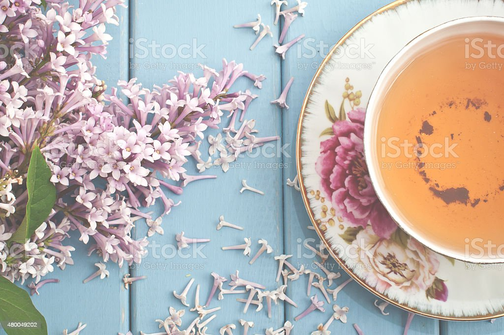 Summer blooming bouquet and a cup of black tea stock photo