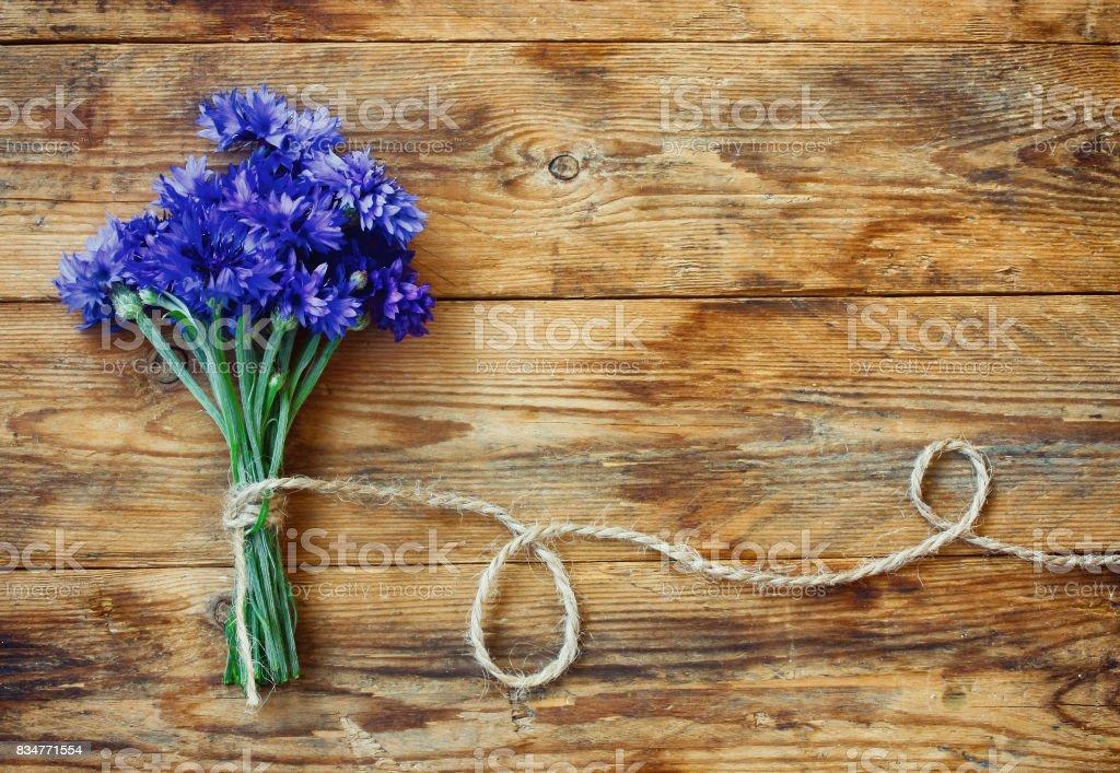 Bouquet d'été de bleuets avec la corde sur la table en bois - Photo