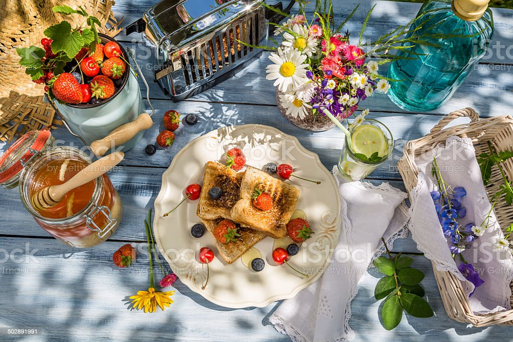 Summer breakfast in the garden with fruit toast with honey stock photo
