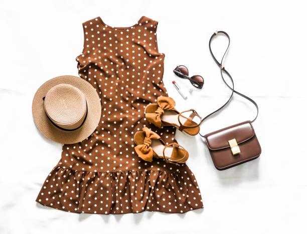 Sommer braun Polka Dot ärmelloses Kleid, Wildleder Sandalen, Leder Umhängetasche, Sonnenbrille und Hut auf einem hellen Hintergrund, Top-Ansicht – Foto