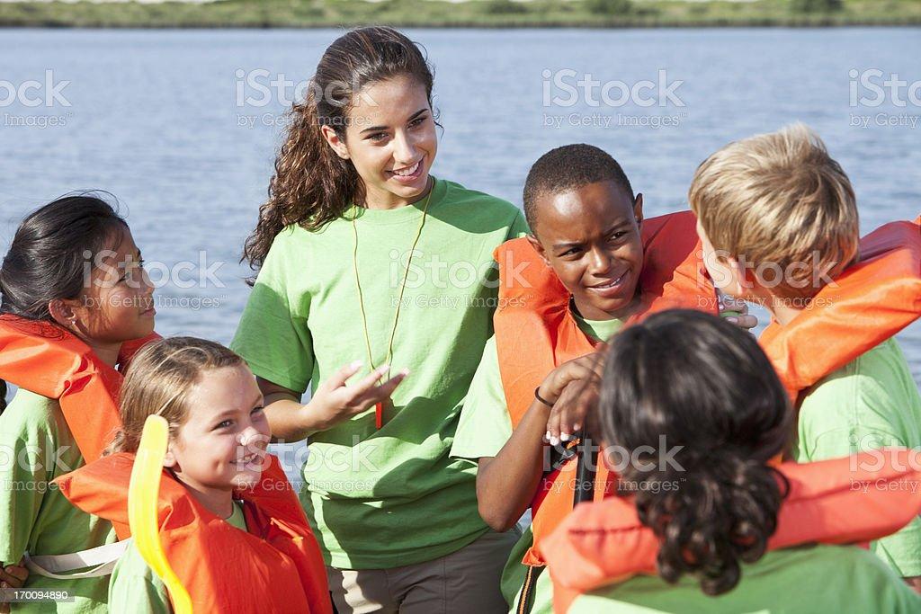 Été Animateur de colonie de vacances qui parle aux enfants portant des gilets de sauvetage - Photo