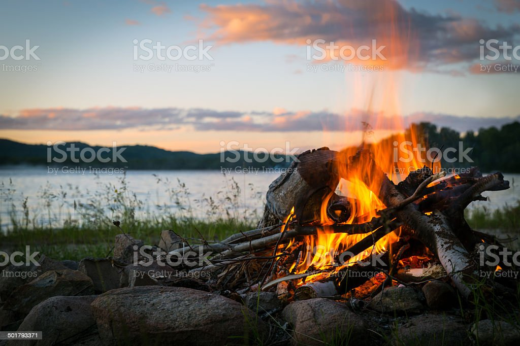 Summer Campfire and Lake at sunset stock photo