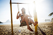 beautiful young woman enjoying the summer on the beach on a swing