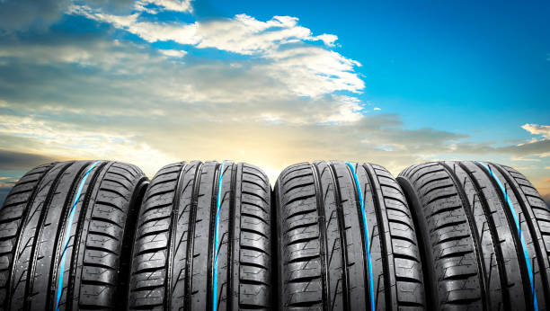 Summer car tires on over blue sky with clouds. Tire stack background. Car tyre protector close up. Black rubber tire. Brand new car tires. Close up black tyre profile. Car tires in a row stock photo