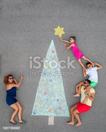 family of four posing for their funny alternative creative christmas card drawing chalk on concrete floor