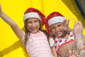 two little girls in inflatable slide wearing christmas hats