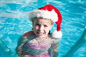 Little girl wearing santa hat in the pool for an Australian summer Christmas