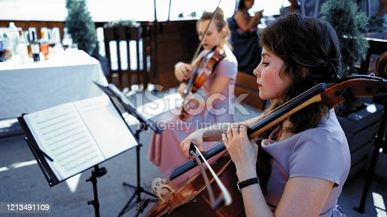 String Quartet In Lilliac Dresses Taking Part In Classical Event Or Wedding Ceremony Outside Summer Terrace