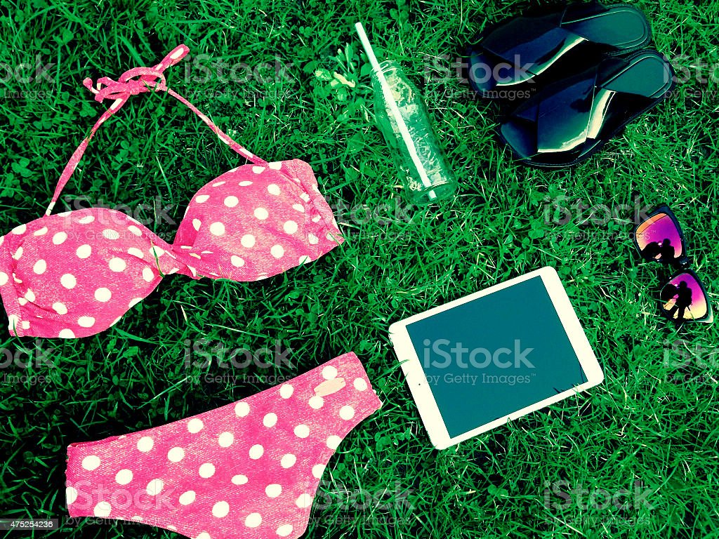 summer clothes swimsuit, tablet, sunglasses, flip flops, glass bottle stock photo
